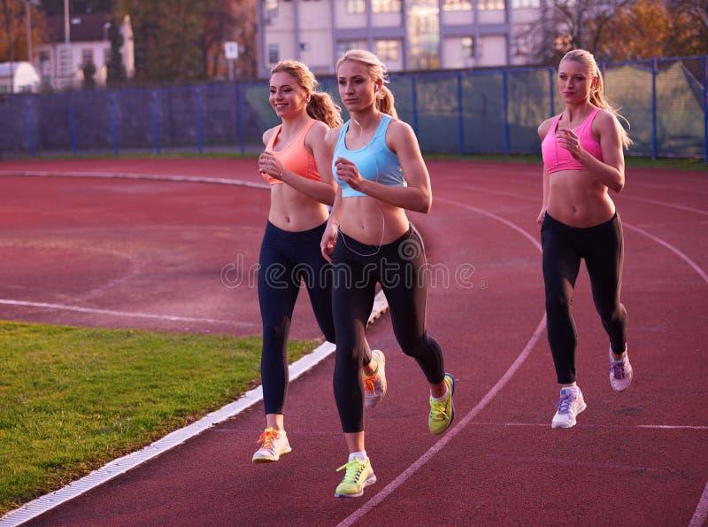 Grupo da mulher do atleta que corre no autódromo do atletismo fotos de stock
