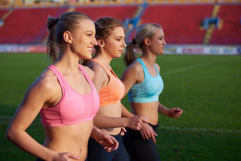Grupo da mulher do atleta que corre no autódromo do atletismo fotografia de stock royalty free