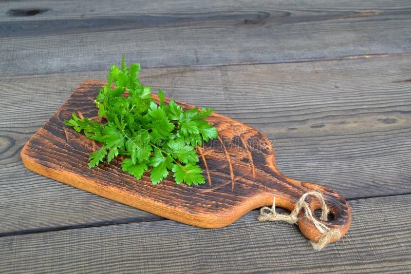 Grupo da salsa orgânica fresca em uma placa de corte em uma tabela de madeira Tabela preta rústica do vintage Alimento verde saud imagem de stock royalty free