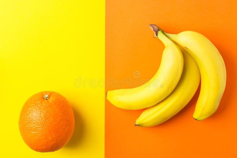 Grupo das bananas maduras amarelas alaranjadas no fundo do duotone Configura??o lisa na moda criativa Tema tropical Comer limpo d foto de stock royalty free