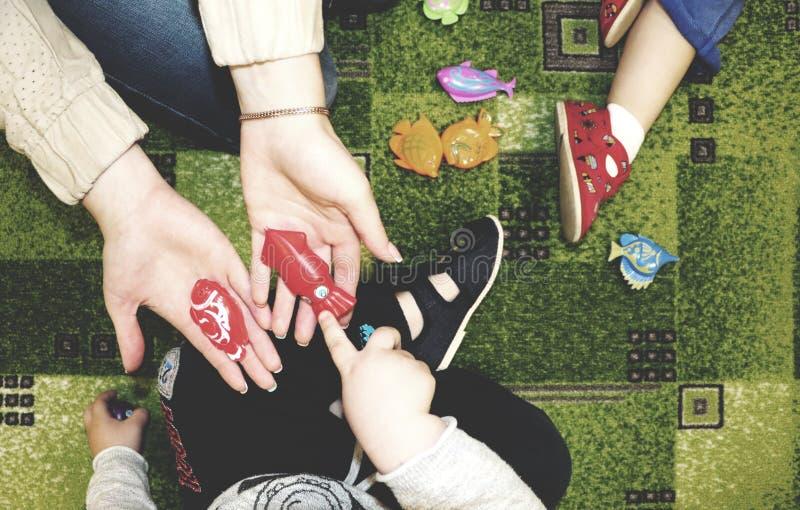 Grupo das crianças que faz artes e ofícios no jardim de infância Crianças que passam o tempo no centro de centro de dia com o gra imagens de stock