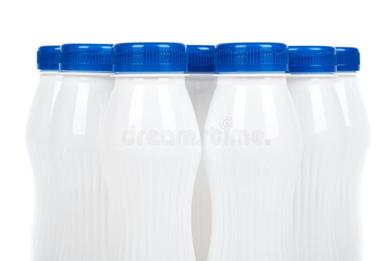 Grupo das garrafas plásticas brancas com iogurte ou leite da bebida Isolado no fundo branco Molde da mercadoria do recipiente, im fotografia de stock royalty free