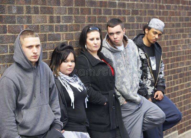 Grupo das juventudes que inclinam-se na parede fotografia de stock