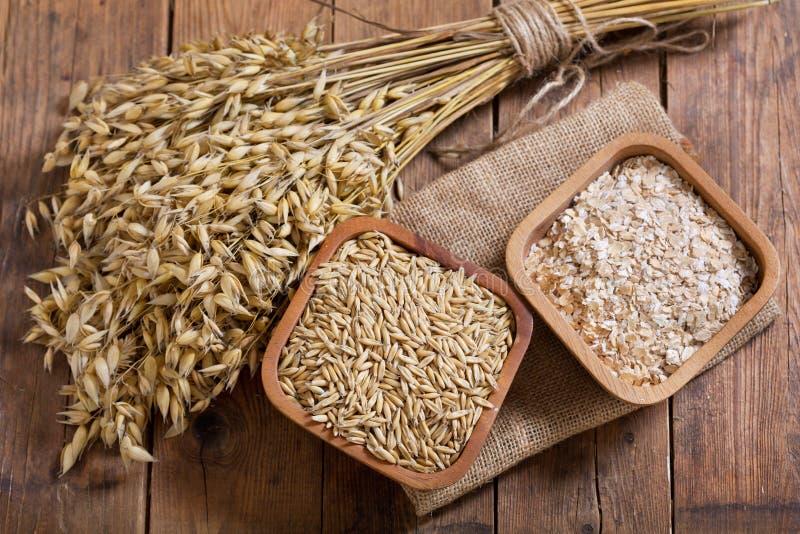 Grupo das orelhas, dos cereais e das grões da aveia na tabela de madeira foto de stock