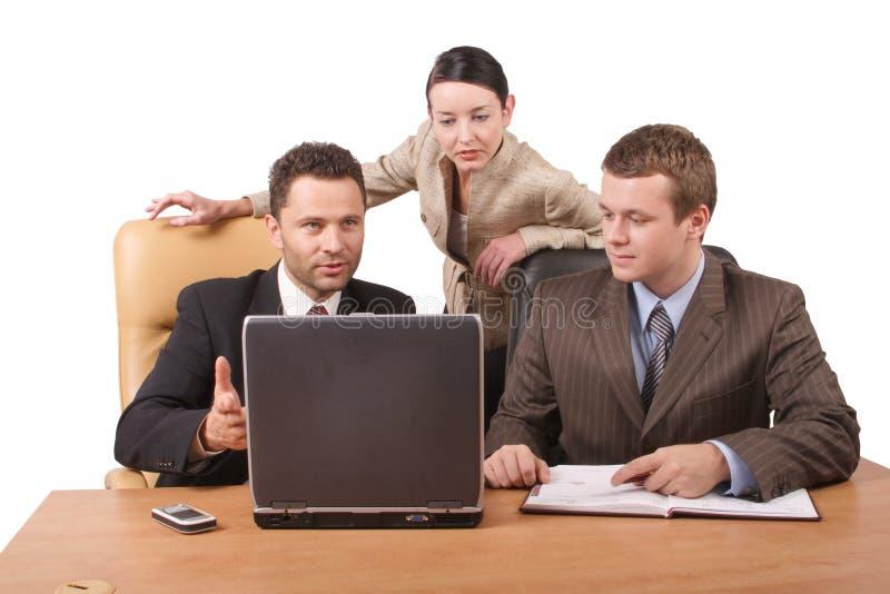 Grupo de 3 executivos que trabalham junto com o portátil no escritório - horizontal, isolado fotografia de stock royalty free