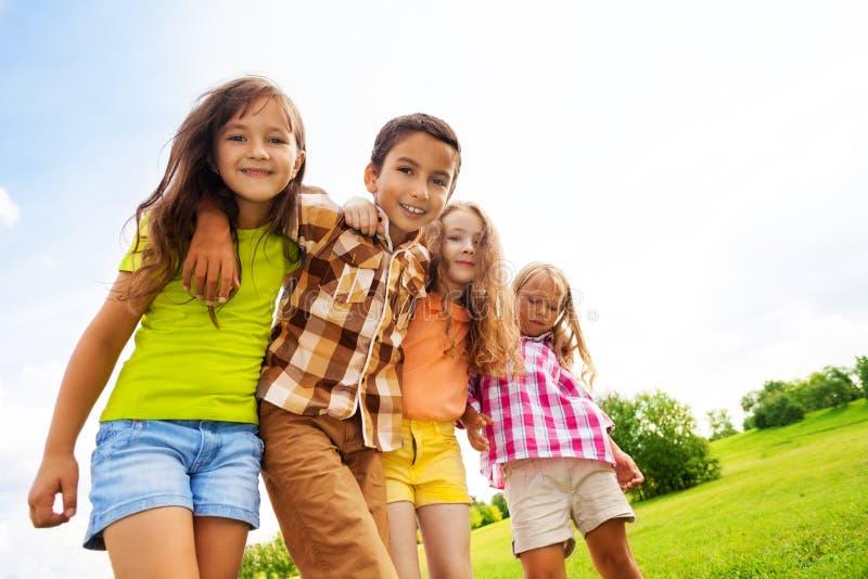 Grupo de abrazar 6, 7 años de niños foto de archivo
