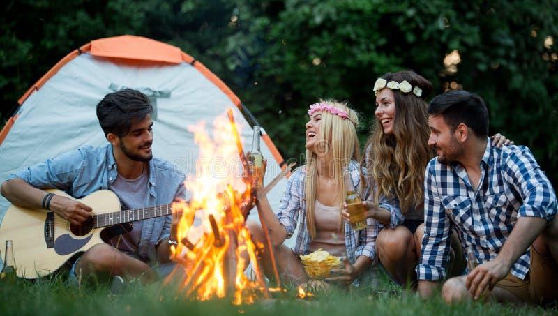 Grupo de acampamento dos amigos Estão sentando-se em torno do fogo do acampamento, jogando a guitarra fotografia de stock royalty free