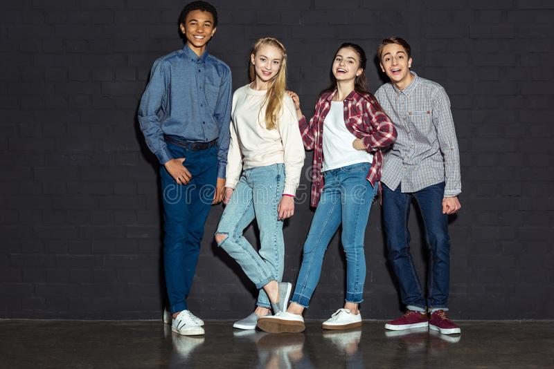 grupo de adolescencias elegantes que se unen y que miran la cámara imágenes de archivo libres de regalías