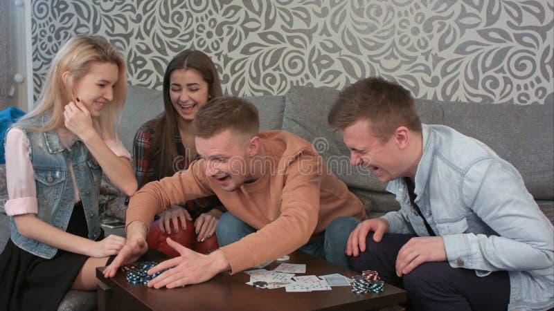 Grupo de adolescencias que acaban el juego de póker, abriendo sus tarjetas y reconociendo al ganador foto de archivo libre de regalías