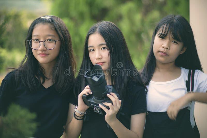 Grupo de adolescente asiático com câmera do dslr à disposição imagens de stock royalty free