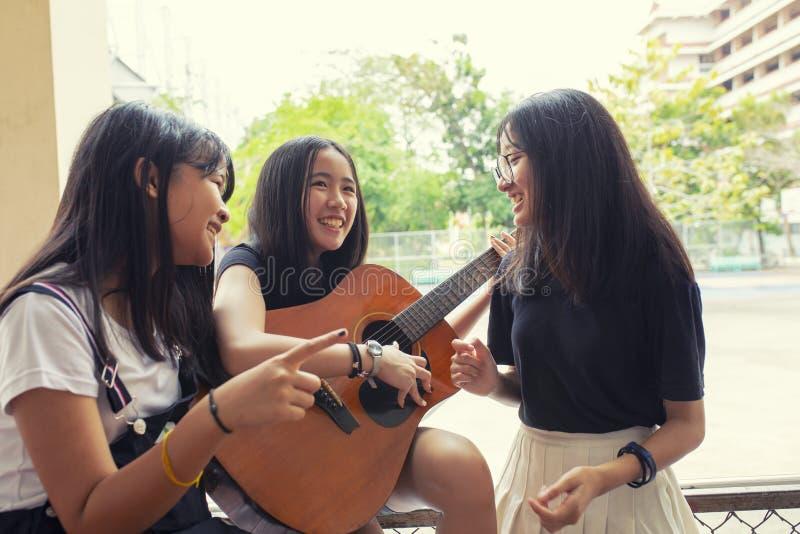 Grupo de adolescente asi?tico que est? exterior exercendo a guitarra espanhola e dan?ando com emo??o da felicidade imagens de stock