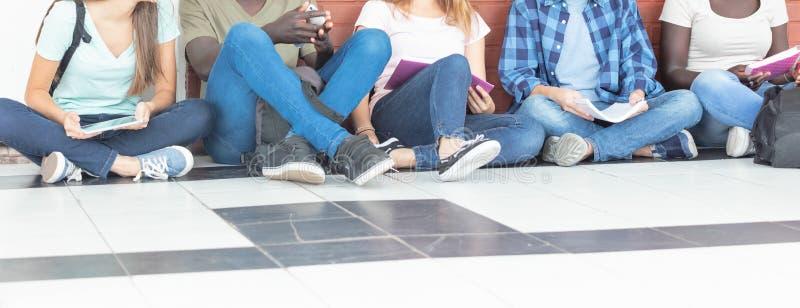 Grupo de adolescentes étnicos multi asentados en el vestíbulo, e que habla imagen de archivo libre de regalías