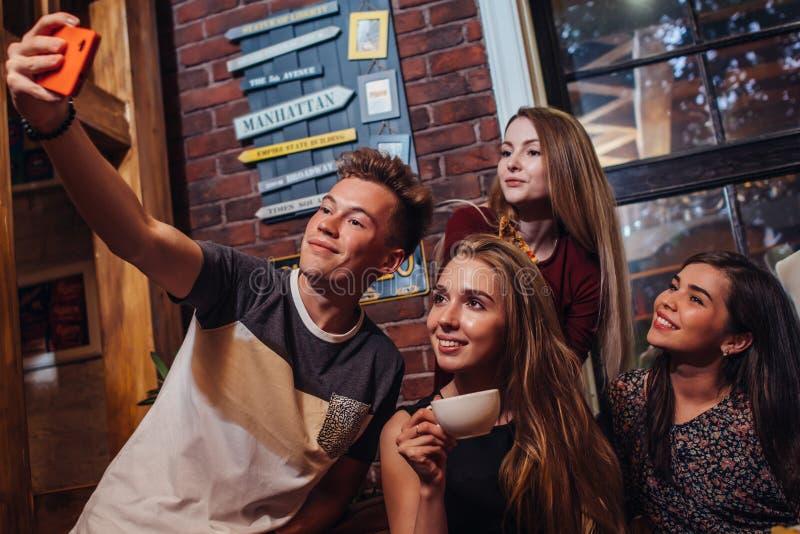Grupo de adolescentes atrativos de sorriso que vestem o equipamento ocasional que toma o selfie com chá bebendo do telefone celul imagem de stock