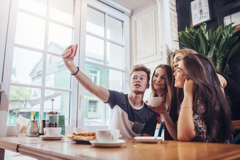 Grupo de adolescentes bonitos que tomam o selfie com telefone celular ao sentar-se em um restaurante com interior no estilo retro foto de stock