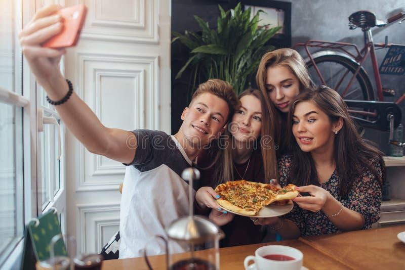 Grupo de adolescentes bonitos que tomam o selfie com telefone celular ao sentar-se em um restaurante com interior no estilo retro imagem de stock royalty free