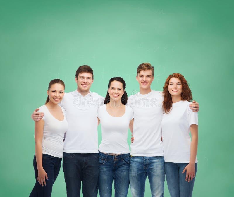 Grupo de adolescentes de sorriso nos t-shirt vazios brancos imagem de stock royalty free