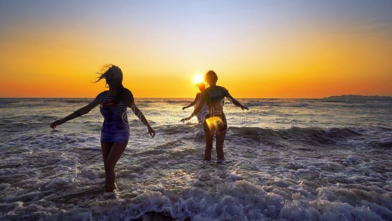 Grupo de adolescentes fêmeas que têm o divertimento que salta e que espirra abaixo da praia imagens de stock