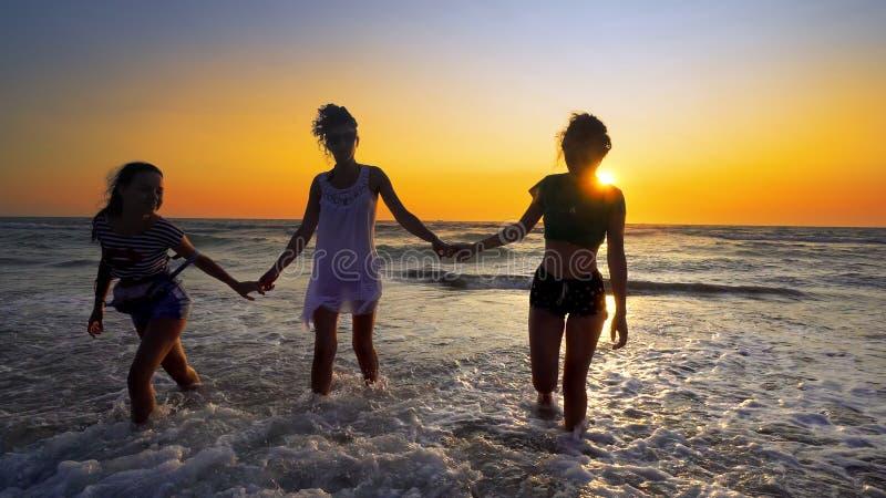 Grupo de adolescentes fêmeas que têm o divertimento que salta e que espirra abaixo da praia fotografia de stock royalty free