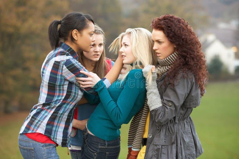 Grupo de adolescentes fêmeas que tiranizam a menina imagens de stock