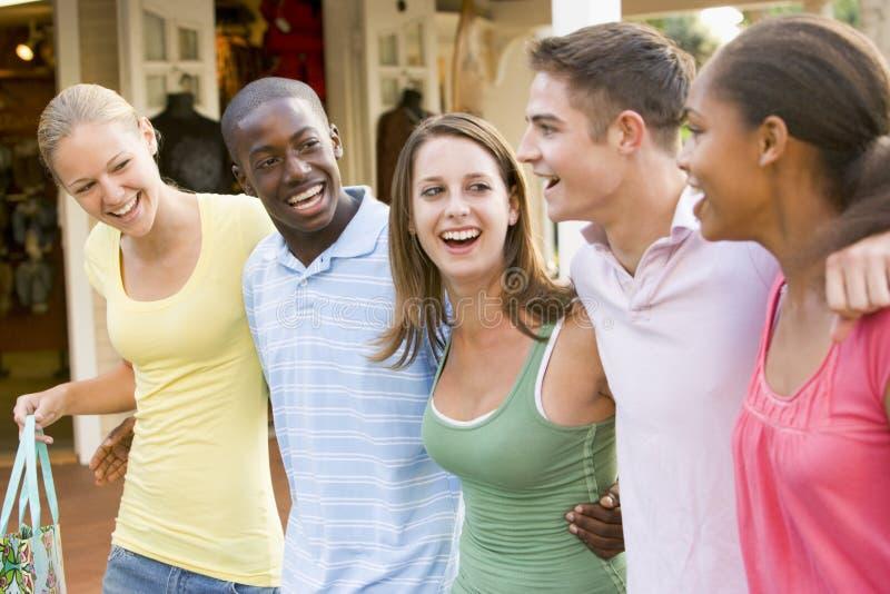 Grupo de adolescentes hacia fuera que hacen compras imagen de archivo libre de regalías