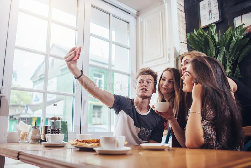Grupo de adolescentes lindos que toman el selfie con el teléfono móvil mientras que se sienta en un restaurante con el interior e foto de archivo