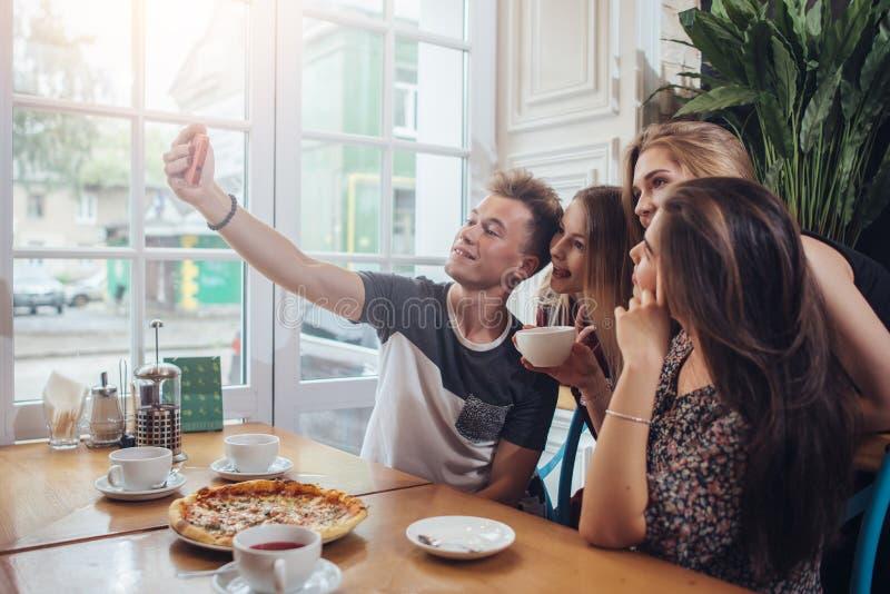 Grupo de adolescentes lindos que toman el selfie con el teléfono móvil mientras que se sienta en un restaurante con el interior e imagenes de archivo
