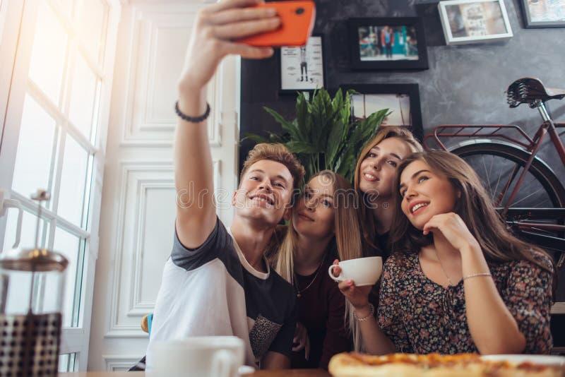 Grupo de adolescentes lindos que toman el selfie con el teléfono móvil mientras que se sienta en un restaurante con el interior e fotos de archivo libres de regalías