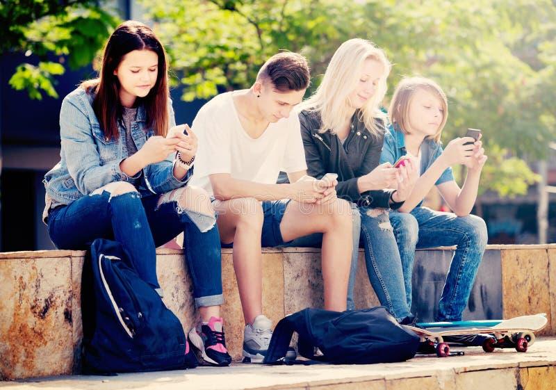 Grupo de adolescentes novos que sentam-se com telefones fotografia de stock royalty free