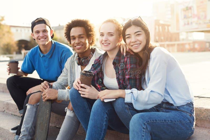 Grupo de adolescentes que cuelgan hacia fuera en parque del pat?n foto de archivo