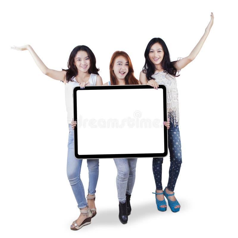 Grupo de adolescentes que guardam uma placa vazia fotografia de stock royalty free