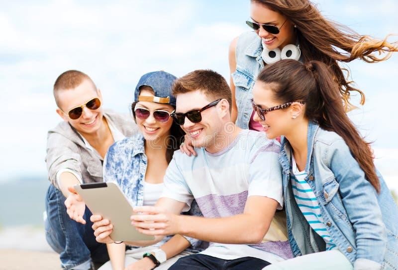 Grupo de adolescentes que olham o PC da tabuleta imagens de stock royalty free