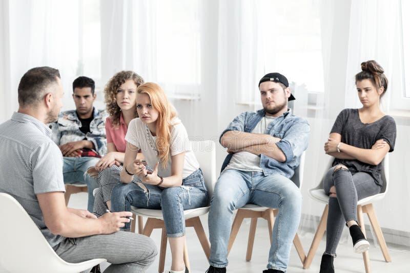 Grupo de adolescentes que pedem seu professor a ajuda com um difficul foto de stock