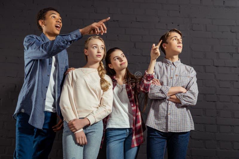 grupo de adolescentes que señalan en alguna parte delante de negro imagen de archivo