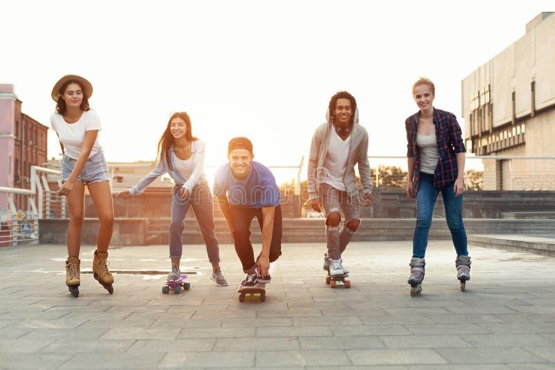 Grupo de adolescentes sonrientes con los pcteres de ruedas y el monopatín imagen de archivo