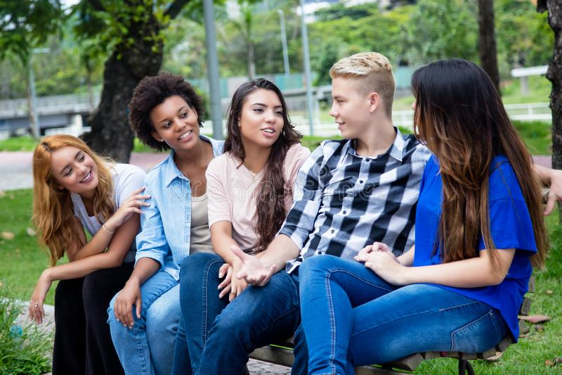 Grupo de adultos jovenes latinoamericanos y africanos que hablan imagen de archivo