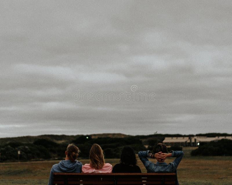 Grupo de adultos jovenes que se sientan en un banco y que disfrutan de la vista de señales y del cielo gris fotos de archivo libres de regalías