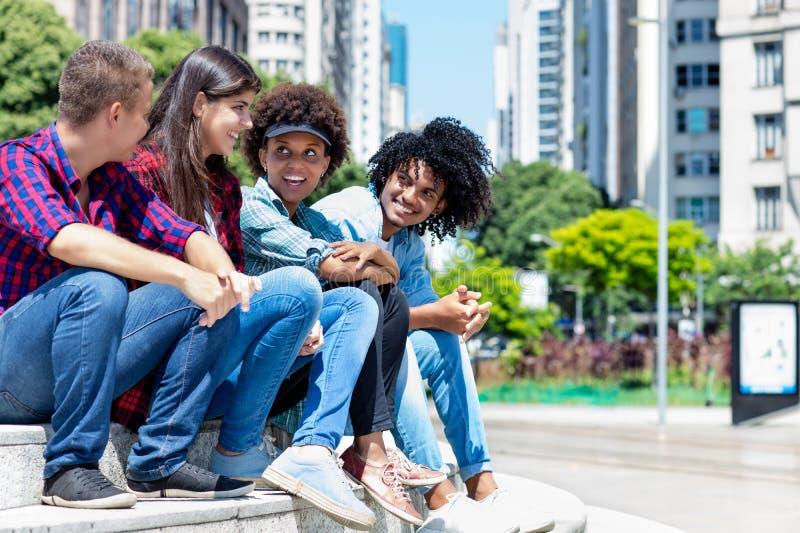 Grupo de adultos novos do moderno latino-americano e afican na discussão na cidade imagens de stock