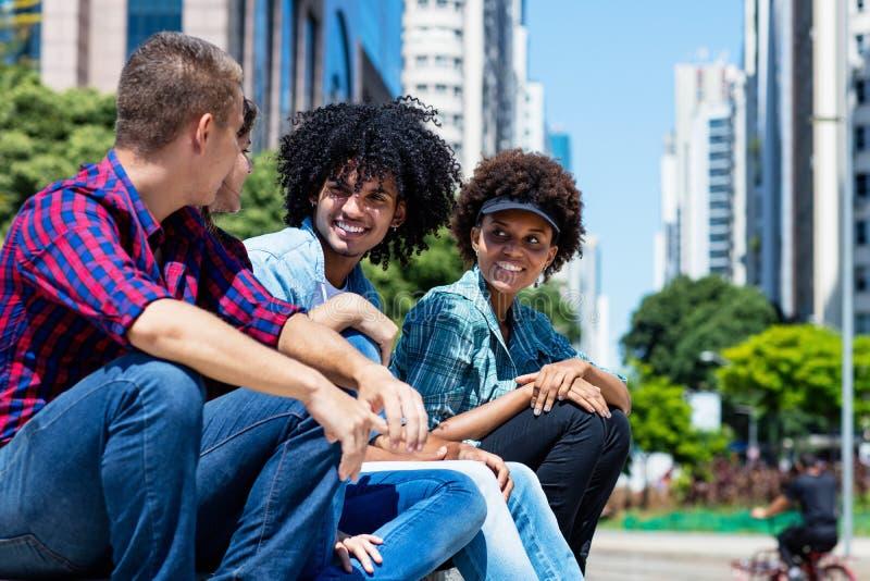 Grupo de adultos novos do moderno que penduram para fora na cidade imagem de stock royalty free