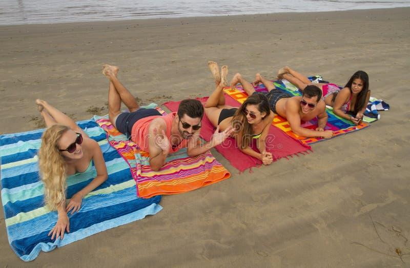 Grupo de adultos novos na praia imagem de stock royalty free