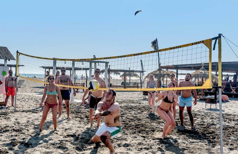 Grupo de adultos que jogam Valleyball na praia fotos de stock royalty free
