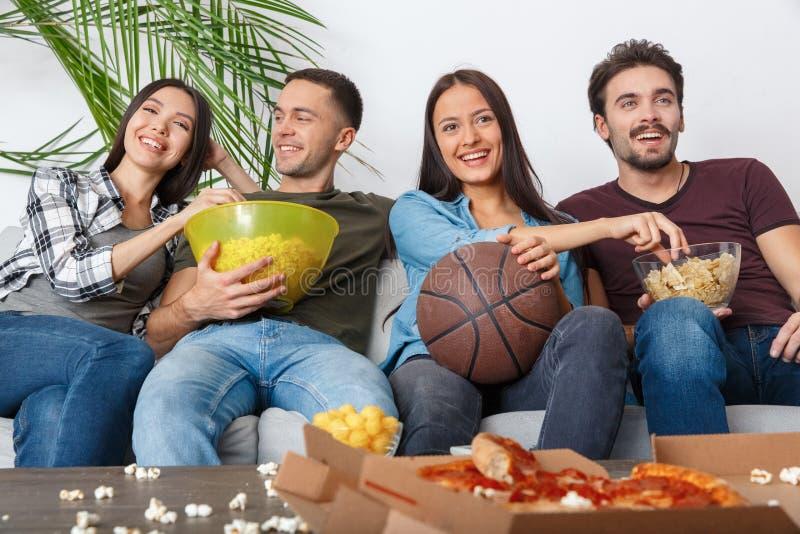 Grupo de aficionados deportivos de los amigos que mira el juego de baloncesto que come los bocados imagenes de archivo
