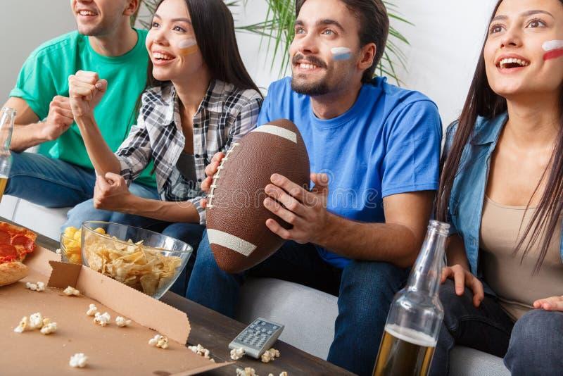 Grupo de aficionados deportivos de los amigos que mira el partido en fútbol americano de las camisas coloridas imagenes de archivo