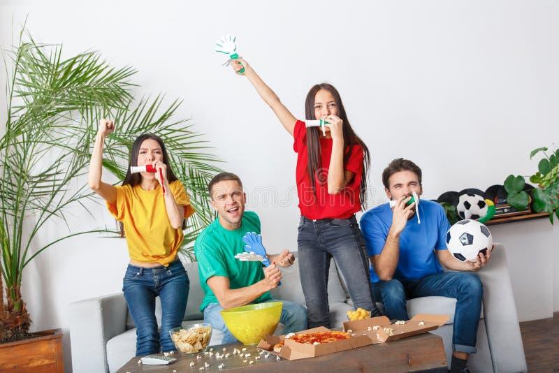 Grupo de aficionados deportivos de los amigos que mira el partido en las camisas coloridas que sostienen los cuernos y las chapal imagen de archivo libre de regalías