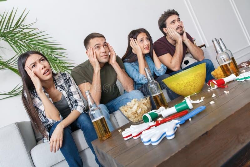 Grupo de aficionados deportivos de los amigos que mira el partido de fútbol el llevar a cabo de la cabeza foto de archivo