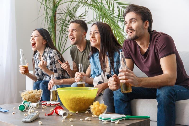 Grupo de aficionados deportivos de los amigos que mira vista lateral del equipo del partido de fútbol que anima fotos de archivo