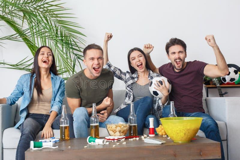 Grupo de aficionados desportivos dos amigos que olha a gritaria do fósforo de futebol alegre foto de stock royalty free