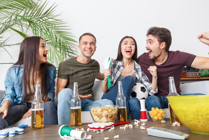 Grupo de aficionados desportivos dos amigos que olha o aperto do fósforo de futebol alegre imagens de stock