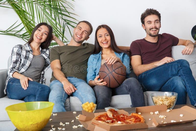 Grupo de aficionados desportivos dos amigos que olha o jogo de basquetebol cronometrar junto imagens de stock royalty free