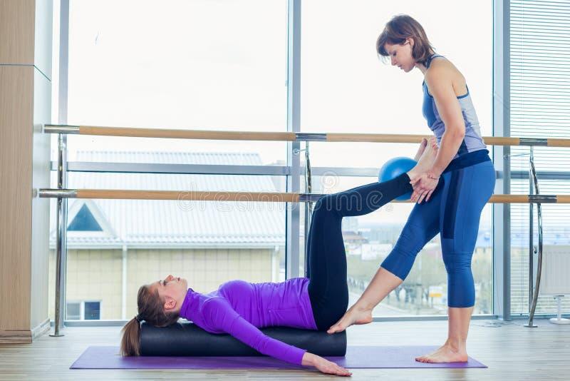 Grupo de ajuda das mulheres do instrutor pessoal de Pilates da ginástica aeróbica em uma classe do gym imagens de stock royalty free