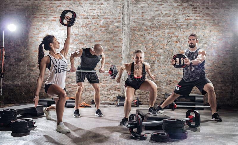 Grupo de ajuste y gente muscular que practica con el barbell foto de archivo libre de regalías